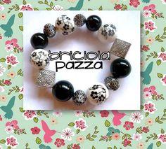 Bracciale elastico realizzato con perle in resina, ceramica dipinta e argentone.
