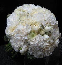 White Carnations, rannuculus, and white roses makes for a very soft bouquet