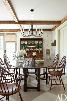 A contemporary oak dining table is paired with Windsor chairs from Nantucket House in the family room