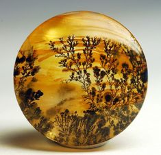 "Dendrite landscape cabochon. ""An agate that looks like a painting of flowering vines silhouetted on a beautiful golden sunset background."""