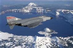Air Force McDonnell Phantom II fighter (s/n c/n form the Fighter Wing The Happy Hooligans, North Dakota Air National Guard, flies over Crater Lake, Oregon (USA). Military Jets, Military Aircraft, Air Fighter, Fighter Jets, Us Navy Blue Angels, Iran Air, Crater Lake Oregon, F4 Phantom, Aircraft Photos