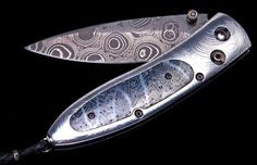 From William Henry knives. The Monarch 'Lava' features a beautiful hand-forged frame in 'Tribal Ladder damascus by Zoe Crist, inlaid with 100,000 year-old fossil coral. The blade is hand-forged 'Typhoon' damascus by Rob Thomas. The one-hand button lock and the thumb stud are set with spinel.