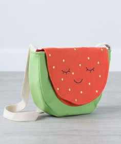 A colorful shoulder satchel that can carry so many treasures and toys wherever your little needs to go! Our Watermelon Satchel is made of soft but sturdy combed canvas fabric and features embroidered appointments like seeds and a serene smiling face. The sewn-on shoulder strap is made to last and the easy-to-open velcro clasp is a snap! A Hallmark Baby exclusive.