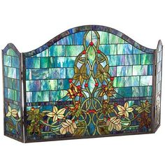 Enjoy a glowing piece of art on a cold winter's evening by setting up this colorful fireplace panel. The floral design is made of dozens of pieces of blue and green glass. The fire will light up the glass and add beauty to your living room.