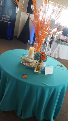 Teal Beach Themed Table Linen With Coral Sticks And Candle Centerpieces.