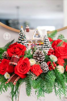 Home for the holidays! An instant Christmas classic, this lush arrangement of red roses and fresh winter greens accompanies a festively patriotic Thomas Kinkade collectible with light-up windows and hand-painted details. This arrangement includes red roses, miniature red roses, white button spray chrysanthemums, seeded eucalyptus, noble fir, and flat cedar. Delivered with Teleflora's Thomas Kinkade's Hero's Welcome Keepsake.