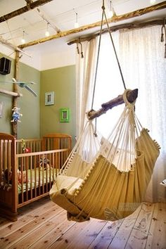 Nursery by Inga Romberga (IngaBerga) | rustic nursery | indoor swing | nursery with green wall and natural wood crib | indoor hammock | sheer window curtains |
