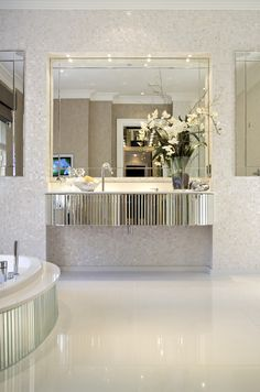 Bevelled mirror floating vanity unit and semi-sunken bath create Art Deco glamour in master bathroom © Hill House Interiors