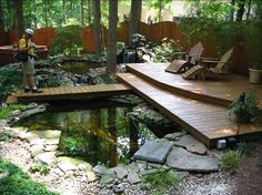 A Koi Pond with a small waterfall and a deck.