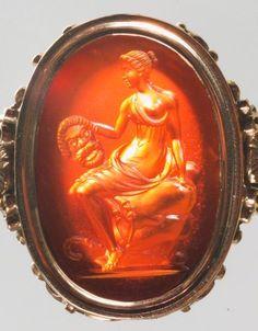 Gemme: Muse mit einer Komödienmaske. Römisch, Republikanisch 3. Viertel 1. Jh. v. Chr. Karneol, dunkelorangefarben, klar, durchscheinend. In moderner Goldfassung als Ring.