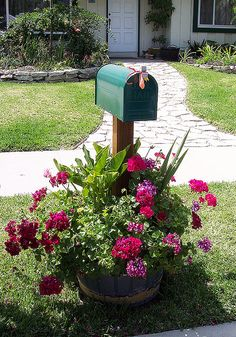 Mailbox with geraniums in whiskey barrel