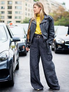 Natalie Hartley pairs a yellow turtleneck with a vintage moto jacket, high-waisted herringbone trousers, metallic heels, and a studded belt