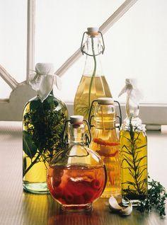 Verschiedene selbstgemachte Essige & Öle - von links nach rechts: Estragonöl, Knoblauch-Chili-Essig, Dillessig, Himbeeressig, Lorbeer-Thymian-Öl