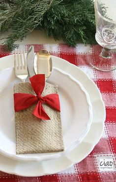 These elegant burlap utensil holders with the pretty red bow make any Christmas tablescape look amazing!  Holiday decor ideas