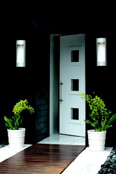 I love this- black house, white door and those planters--- are those orchids? perfection: simple is so hard to pull off