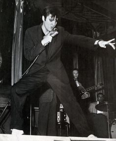 Elvis Presley sharply dressed in black and wearing spotless all-white shoes is pictured performing live at the Pennsylvania Sports Arena in Philadelphia, PA on Friday April 5, 1957. Scotty Moore on guitar and D. J. Fontana can be seen in the background. See more at: http://scottymoore.net/philadelphia.html