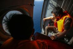 Vietnamese military personnel look out of a helicopter during a search and rescue mission off Vietnam's Tho Chu island, March 10, 2014. REUTERS/Athit Perawongmetha