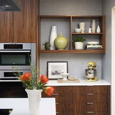Inspiration for a mid-sized midcentury l-shaped eat-in kitchen in San Francisco with an undermount sink, flat-panel cabinets, medium wood cabinets, quartzite benchtops, white splashback, ceramic splashback, stainless steel appliances and an island.