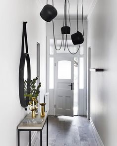 Minimalist entryway with light gray floors, a black mirror, and layered pendant lights