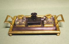 """An early 19th Century Regency period Bronze and Ormolu Desk-set having wafer box with """"taperstick"""" lid flanked by glass inkwells, all contained in bronze stand with ormolu framing and attractive splayed carrying handles. (c. 1840 England)"""