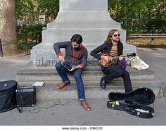 A musician playing the mandolin duets with aother musician playing the ipad app node beat on a Mac laptop computer. - Stock Image
