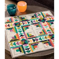 Dive into your scrap basket to make this showstopping quilt by Carrie Nelson, featuring small versions of classic Log Cabin blocks and flying-geese units.