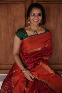 A Vibrant maroon silk with orange border and green selvedge, mandala motifs in zari across the spread makes the saree an auspicious ensemble with complete zari weave in pallu. Kerala Saree Blouse Designs, Half Saree Designs, Saree Blouse Neck Designs, Bridal Blouse Designs, Simple Sarees, Trendy Sarees, Fancy Sarees, Bridal Sarees South Indian, Indian Sarees