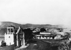 "Our Lady of the Angels Church, known as ""The Old Plaza Church"", is on the left, facing the Los Angeles Plaza. Photograph taken in 1868. Note that the bell wall has been replaced by a gazebo-like structure mounted on the roof."