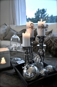 Lots of different candles and cookie jars on a couch table