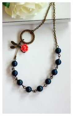 Dragonfly Garden.  An Oxidized brass Dragonfly, Coral Flower, and Dark Blue Swarovski Pearl Necklace.  For Her. Mom. Bridesmaid Gifts.. $27.50, via Etsy.