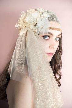 Please note that the current dye lots of the metallic gold tulle is a warm gold almost a bronze shade  This beautiful bridal cap is hand made of two layers of tulle. The bottom layer is beautiful metallic Spanish lace and the top layer is beautiful soft french tulle. Hand trimmed with metallic scalloped Mokuba Lace and hand stitched Preciosa crystal chain. Multiple clusters of hand formed silk organza flowers grace the side of this beautiful veil. Some of the flowers are dusted with…