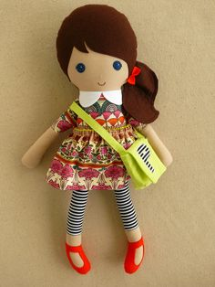 Custom listing for Kate:    This is a handmade cloth doll measuring 20 inches. She is wearing a lovely jewel toned floral dress with striped leggings and orange shoes. She carries a lime green satchel with a striped P on the front. Her dark brown hair is worn in a long, side-ponytail and accented with an orange felt bow. She is made from 100% cotton fabrics, wool blend felt, fleece, and polyester fiberfill. Her seams are triple stitched, and she is firmly stuffed.    Please hand wash only…