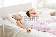 people, family, bedtime and happiness concept - happy couple sleeping in bed at home photo