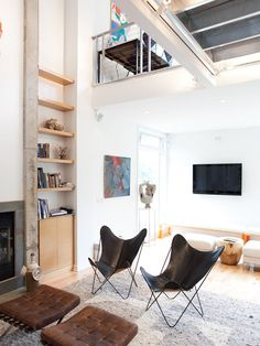 FIREPLACE Living room with black leather butterfly chairs and a concrete-edged fireplace