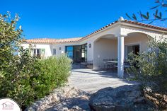 Une maison en L (modèle Valinco) avec terrasse couverte donnant sur cuisine et très belle baie vitrée dans le séjour. Une réalisation Demeures Corses #maison #corse #constructeur