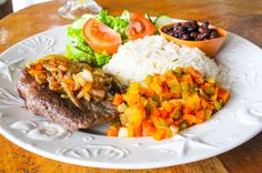 beefsteak casado, $6 comes with a grilled beefsteak topped with sautéed onions, on the side steamed vegetables, rice, black beans and a romaine lettuce, tomato and cucumber salad. Panaderia Delicias Drake town, Osa Peninsula Costa Rica #food #foodie #vacation #travel