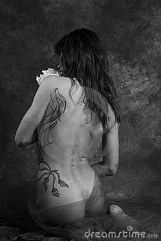 Nude woman with floral tattoos Black and white rear view of nude young woman with flora tattoos, studio background. Photo taken on: November 21st, 2009