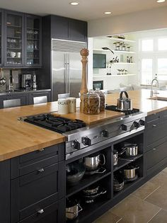 Open cookware storage shelves beneath the cooktop :: perhaps an interesting way to show off that colorful set...