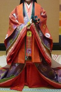 "Putting on kara-ginu and mo - Kouchigi: (lit., ""small cloak"") a shorter brocade robe worn over the uchigi or uwagi to add some formality on occasions when the karaginu and mo were NOT worn. - Karaginu: A waist length Chinese style jacket. - ""Mo"": An apron-like train, down the back of the robe. White with painted/embroidered adornment."