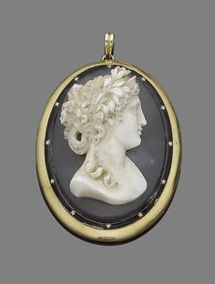 A late 19th century agate cameo pendant  The oval agate plaque carved to depict the bust of a classical maiden facing left, within a black enamel surround highlighted with gold stars, length 6.2cm