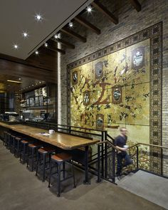 At Oak & Rush in Chicago, Starbucks designers worked with artist Olalekan Jeyifous to create a large 25 panel mural depicting an Oak tree providing shade to a coffee tree, while sharing vignettes of a coffee story rising through its boughs. The mural includes tiles that depict oak leaves, coffee cherries and a coffee bean in a style that is inspired by Chicago's rich architectural tradition.