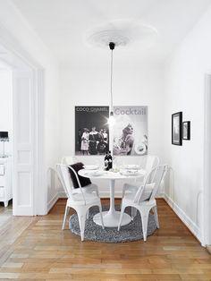 Zona de comedor con paredes blancas, mesa redonda blanca y sillas blancas.