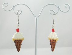 """The item up for sale is a pair of beaded earrings. The design features an a delicious-looking ice cream cone. The main portion of the earring is constructed by hand-weaving together tiny glass beads. The earring hooks are silver-plated surgical steel. The earring measures 3/4"""" wide x 2-1/4"""" high. Earring beaded by: Jennifer Kaspar Earring pattern by: Lynsey James Earring pattern modified by: Jennifer Kaspar"""