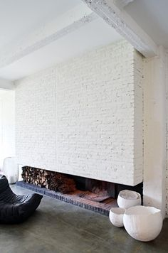 Minimalist white fireplace. Display wood below, something sculptural on hearth, chair beside