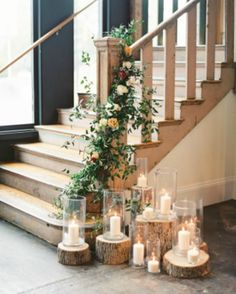 Pretty stair post decorated with flower garland. Tree stumps and hurricanes with white candles.