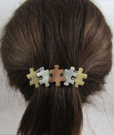 Puzzle piece bronze, silver and gold hairclip that promotes autism awareness.
