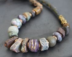 """lampwork beads with gold and silver foil, wonderful ceramic beads by """"etsians"""" GreyBirdStudio, RaggedRobyn and agate, fluorite The cord is handmade of beautiful Thai silk. Each bead is separated with handmade bronze spacers. Metal Clay Jewelry, Ceramic Jewelry, Ceramic Beads, Polymer Clay Beads, Lampwork Beads, Handmade Beads, Handmade Jewelry, Beaded Jewelry, Beaded Necklace"""