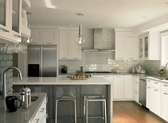 Fantastic two-tone kitchen design with white kitchen cabinets, gray quartz countertops, gray kitchen island, modern counter stools, clear glass gobe pendants and Ann Sacks Savoy Tiles in Cottonwood backsplash