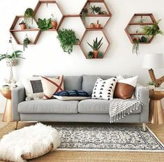Bring a natural feel to your home with hexagonal, wooden shelves filled with plants and all sat above a light grey sofa full of comfort. Add a pile of pillows and you will have the perfect living room to relax in. #remodelinglivingroomideas
