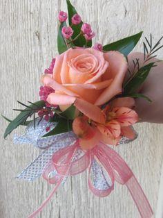 Peach rose, orange alstro,and pink wax flower corsage.